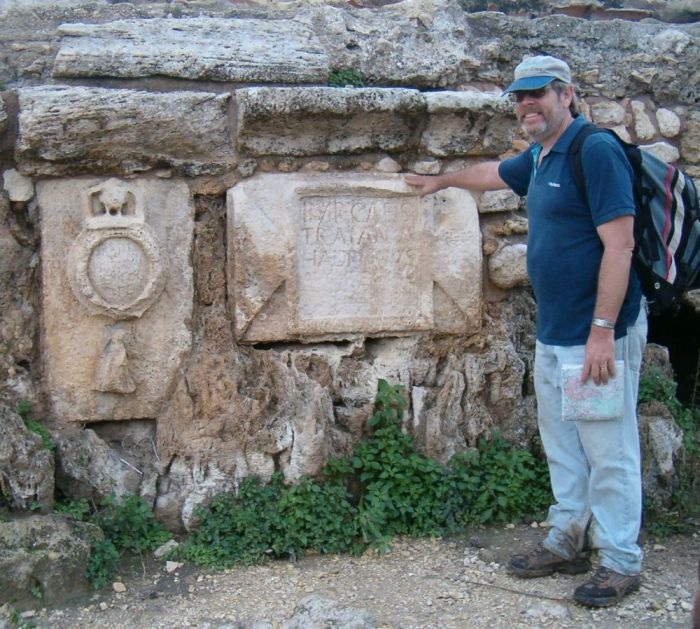 Don standing next to two tablets on the Caesarea Roman aqueduct.