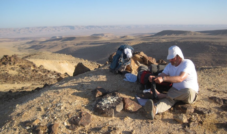 Don taking care of his feet after breakfast with the Machtesh haGadol in the distance.